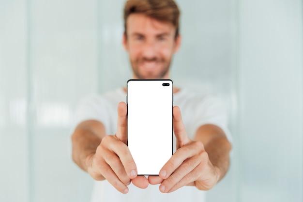 Hombre feliz mostrando teléfono inteligente con maqueta