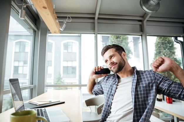 Hombre feliz en la oficina coworking hablando por teléfono.