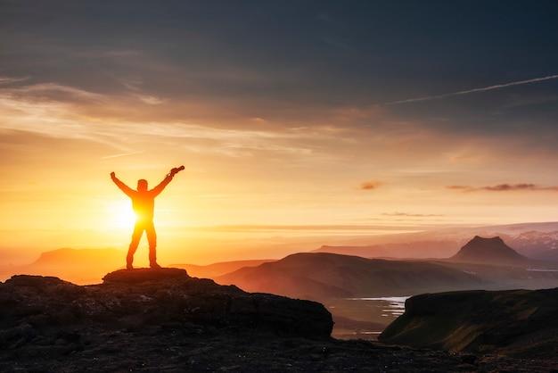 Hombre feliz de pie en un acantilado al atardecer