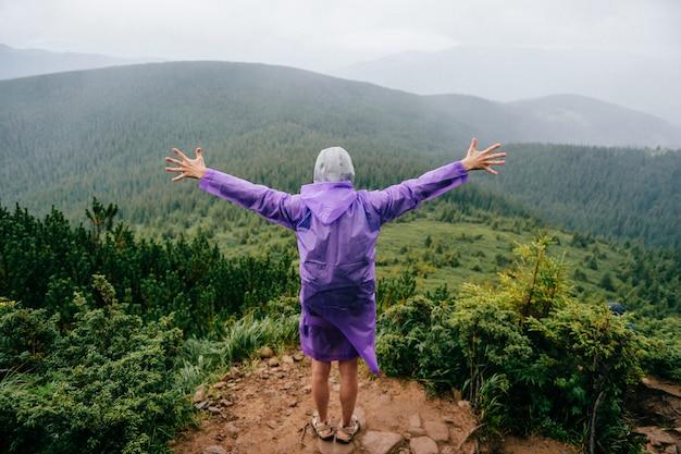 Hombre feliz de pie en la cima de la montaña con las manos separadas
