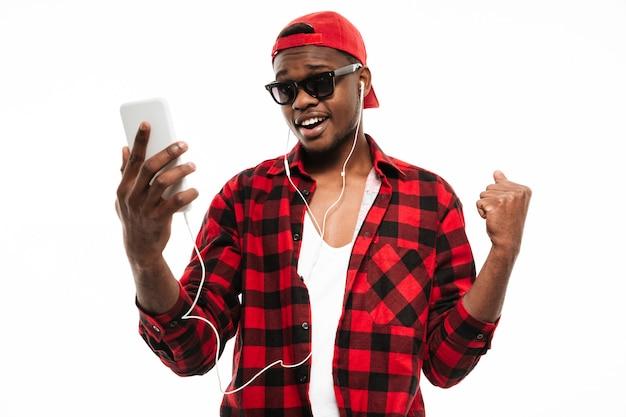Hombre feliz de pie y escuchando música desde el teléfono celular