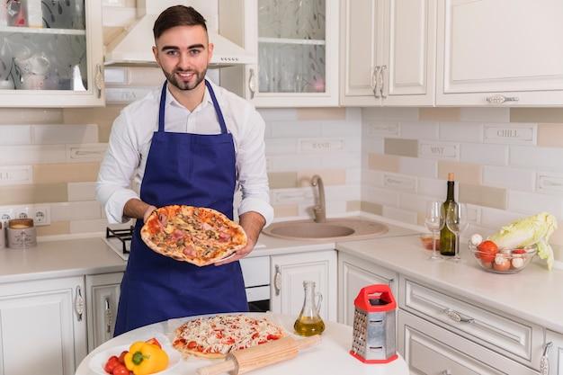 Hombre feliz de pie con pizzas en la cocina