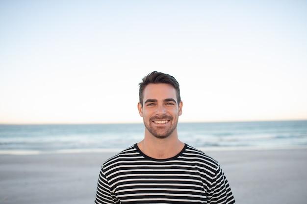 Hombre feliz de pie en la playa
