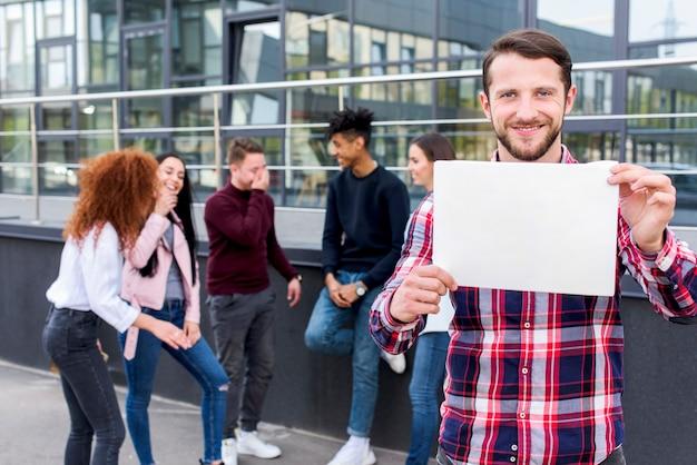 Hombre feliz de pie con sus amigos sosteniendo la tarjeta en blanco en sus manos