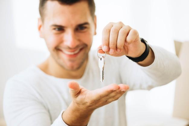 Hombre feliz posando con llaves