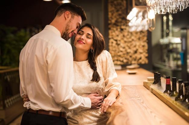 Hombre feliz que abraza a la mujer alegre en el contador de la barra