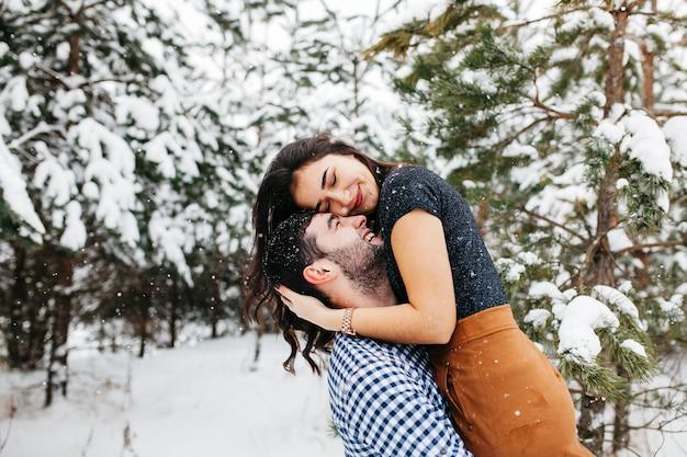 Hombre feliz que detiene a la mujer en brazos en bosque del invierno