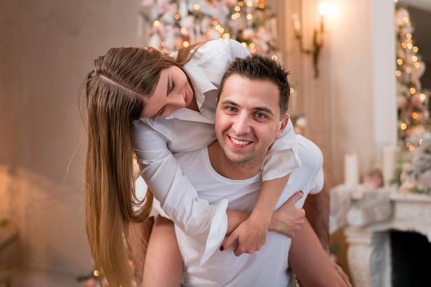 Hombre feliz que lleva a cuestas a la mujer con el árbol de navidad
