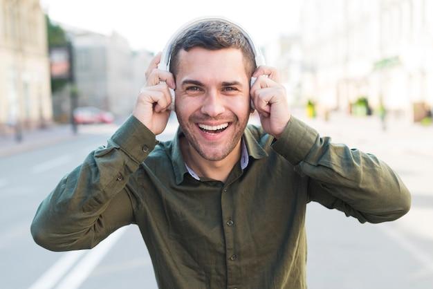 Hombre feliz que lleva música que escucha del auricular y que mira la cámara
