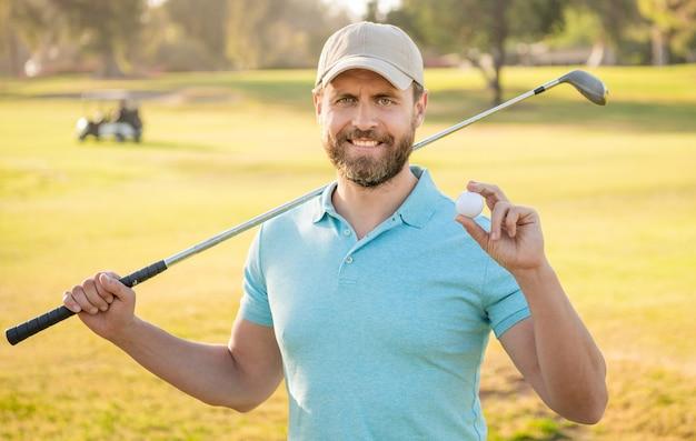 Hombre feliz que muestra la bola del juego de golf en la hierba verde, golf.