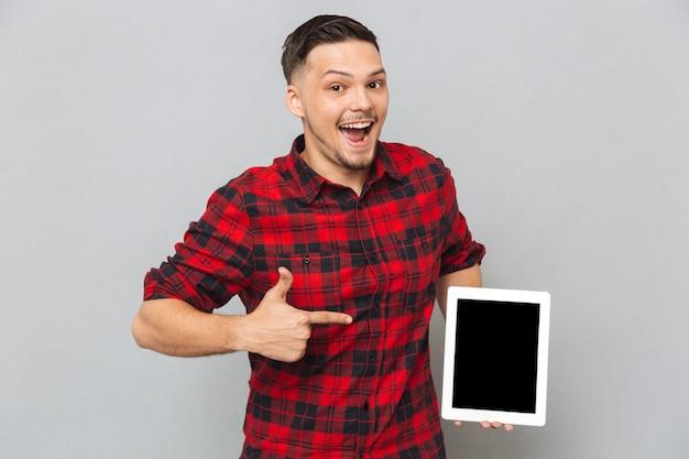 Hombre feliz que muestra la pantalla de la tableta en blanco
