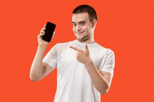El hombre feliz que muestra en la pantalla vacía del teléfono móvil contra la pared naranja