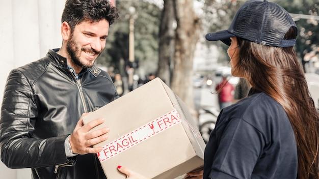 Hombre feliz que recibe el paquete del mensajero femenino