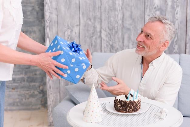 Hombre feliz que recibe el regalo de cumpleaños de su esposa cerca del pastel y del sombrero de fiesta en la mesa