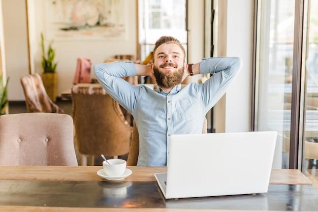 Hombre feliz que se relaja en el café con la taza de café y el ordenador portátil en el escritorio