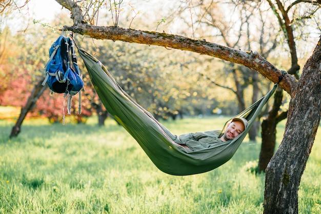 Hombre feliz que se relaja en la hamaca que cuelga en manzano en parque soleado del verano.