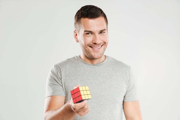 Hombre feliz que sostiene el cubo de rubik.