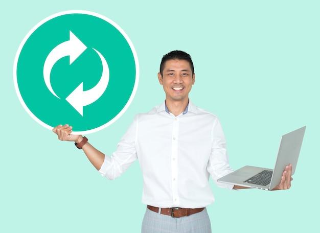 Hombre feliz que sostiene un ordenador portátil y un icono de actualización