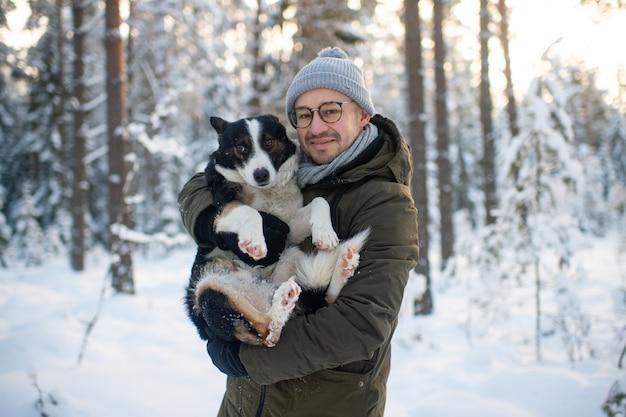 Hombre feliz que sostiene el perro encantador en sus manos en bosque nevoso.