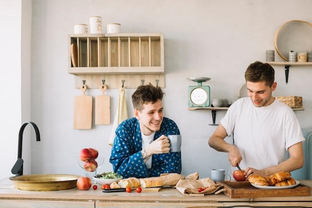 Hombre feliz que sostiene la taza de café y su manzana del corte del amigo en tajadera en cocina