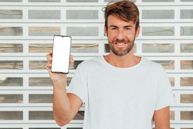 Hombre feliz que sostiene el teléfono celular con maqueta