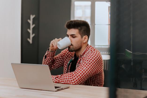 Hombre feliz que trabaja en la computadora portátil y que bebe el café en casa.
