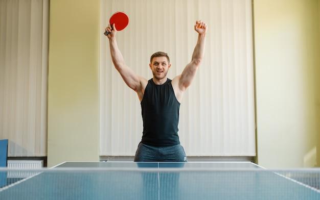 Hombre feliz con raqueta de ping pong levantó las manos, torneo en el interior. persona del sexo masculino en ropa deportiva, formación en club de tenis de mesa