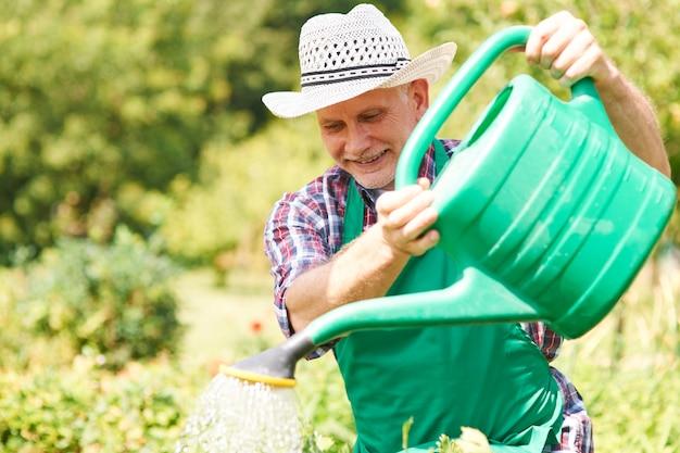 Hombre feliz regando sus plantas en verano