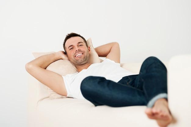 Hombre feliz relajándose en el sofá en casa