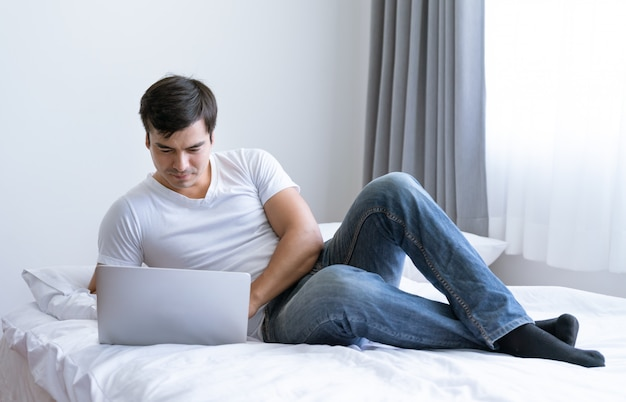 Hombre feliz relex usando laptop en la cama en el dormitorio