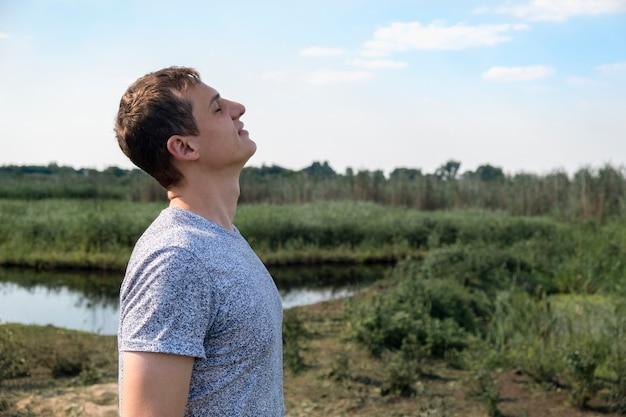 Hombre feliz respirando profundamente aire fresco al aire libre con el lago y el campo en el fondo