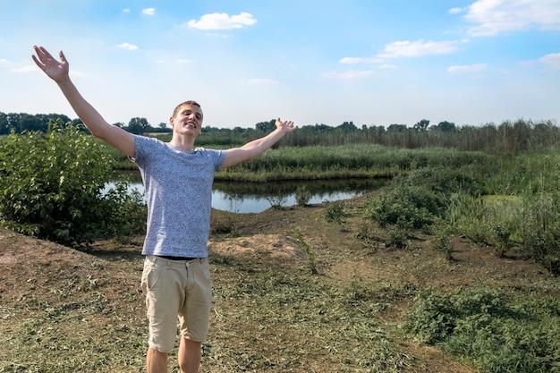 Hombre feliz respirando profundamente aire fresco de pie contra el lago y el campo un día soleado