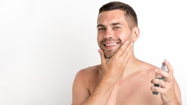 Hombre feliz rociando loción para después del afeitado de pie contra el fondo blanco.