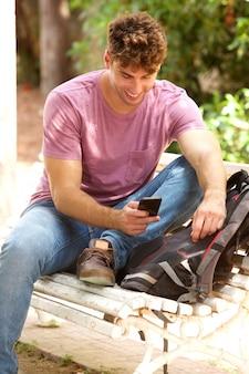 Hombre feliz sentado en el banco del parque con mochila y celular