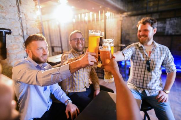 Hombre feliz sentado en un pub y tintineo con vasos llenos de oso.