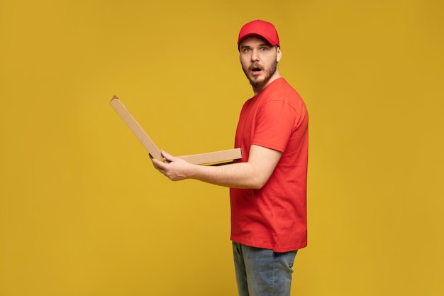 Hombre feliz del servicio de entrega en camiseta roja y gorra dando orden de comida y sosteniendo una caja de pizza aislada sobre una pared amarilla