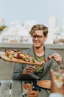 Hombre feliz siendo servido con brochetas veganas de barbacoa