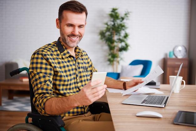 Hombre feliz en silla de ruedas trabajando en casa