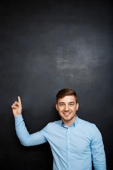 Hombre feliz sobre punto de pizarra con un dedo