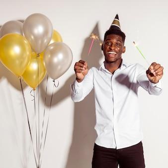 Hombre feliz con sombrero de fiesta y celebración de bengalas