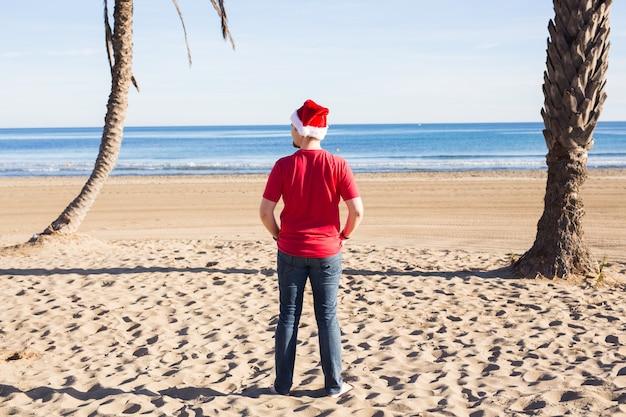 Hombre feliz con sombrero de navidad te mira mientras está de pie en la playa