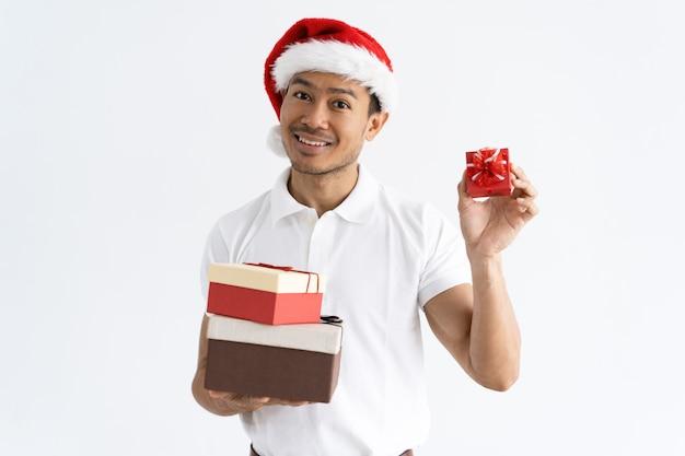 Hombre feliz con sombrero de santa y mostrando cajas de regalo pequeñas y grandes