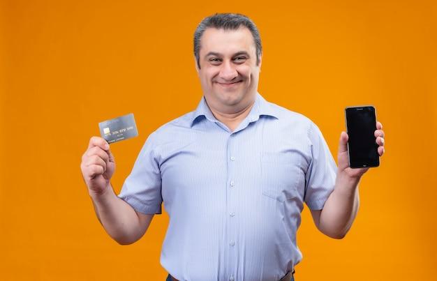 Hombre feliz y sonriente en camisa azul a rayas verticales mostrando tarjeta de crédito y teléfono móvil mientras está de pie
