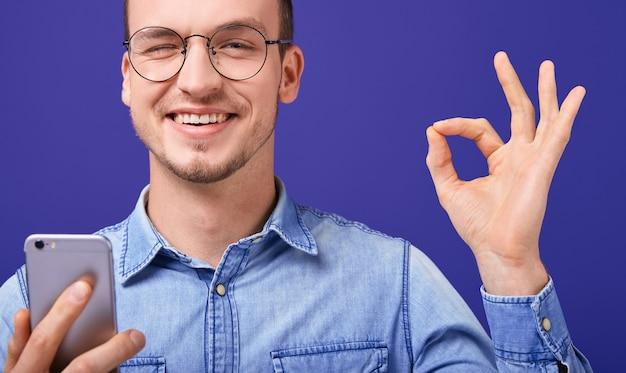 Hombre feliz sonriente en camisa de mezclilla azul guiñando un ojo