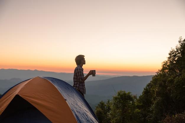 Hombre feliz con sostener una taza de café cerca de la tienda alrededor de las montañas bajo la luz del atardecer