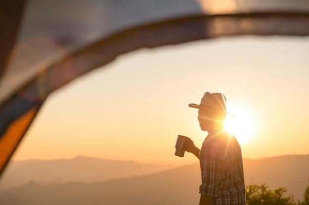 Hombre feliz con sostener una taza de café cerca de la tienda alrededor de las montañas