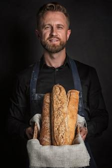 Hombre feliz sosteniendo una canasta con pan