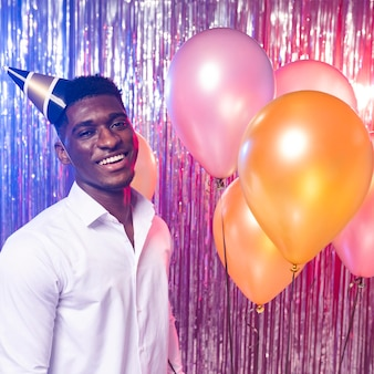 Hombre feliz sosteniendo globos vista frontal y sombrero de fiesta
