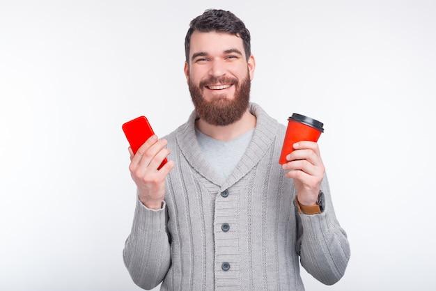 El hombre feliz está sosteniendo su teléfono y una taza roja para ir en el fondo blanco.