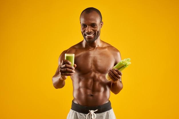 Hombre feliz sostiene vidrio con jugo de apio fresco.